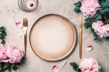 Tableware, flowers for serving a festive table, dinner. Stoneware plates, golden cutlery, eucalyptus branches, peony flowers on marble background. Copy space. Flat lay, top view. Table setting