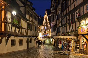 Strasbourg, France. Rue du Bain-aux-Plantes street in Petite France historic quarter in dusk with half-timbered houses decorated for Christmas.