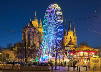 Erfurt, Germany. Ferris wheel at Christmas market on Domplatz (Cathedral Square) on the background of St. Mary's Cathedral and Church of St. Severus in twilight.