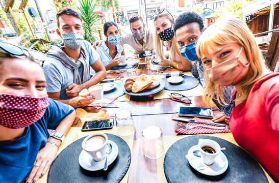 Friends taking selfie at coffee bar - People having fun together at cafeteria covered by face masks - New normal lifestyle concept with happy guys and girls at restaurant cafe - Bright vivid filter