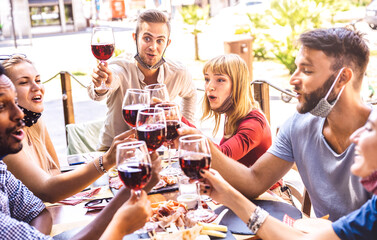 Friends toasting red wine at restaurant bar with face masks - New normal friendship concept with happy people having fun together on sunny day - Bright filter with focus on right blond woman