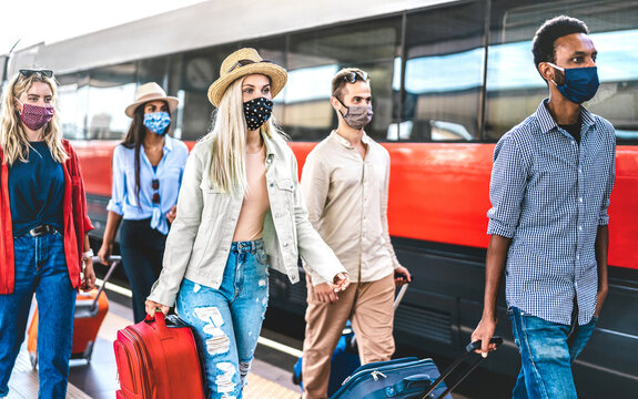 Multiracial friends group walking at railway station platform - New normal travel concept with young travelers on social distancing and face covered by protective mask - Focus on blonde girl with hat