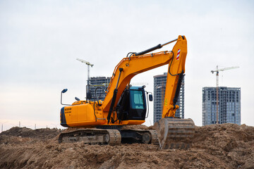Excavators during earthworks at construction site. Backhoe the digging pit for construct building foundation. Paving out sewer line. Construction machinery for excavating, loading, lifting and hauling