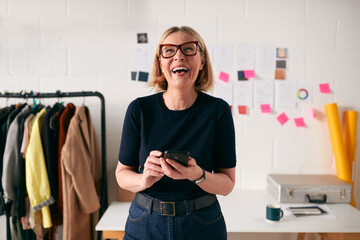Laughing Mature Businesswoman With Mobile Phone In Front Of Desk In Start Up Fashion Business