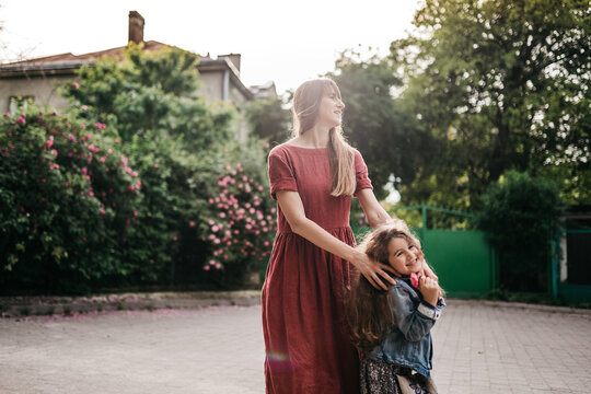 daughter laughs in the arms of mom in the park