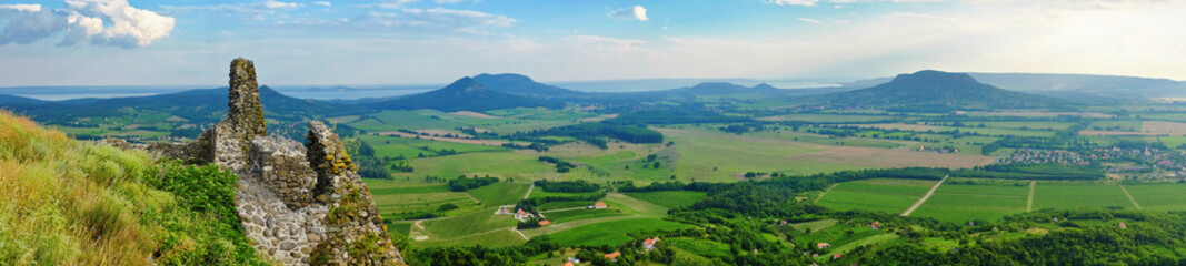 Panoramic photo of lake Balaton and the Badacsony mountains with the Kali basin from the mountain top of Csobanc with castle ruins in the foreground