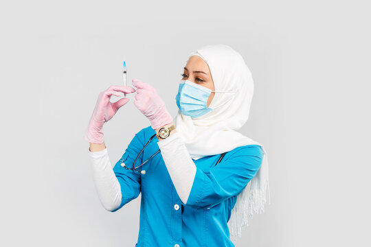Muslim doctor or nurse in hijab and medical face mask holding a syringe on a gray background. the concept of vaccination of the population or injection plastic of the face