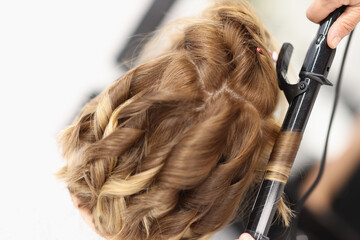 Hair curlers make curls on women's hair. Services of a hairdresser for evening and festive hairstyles concept