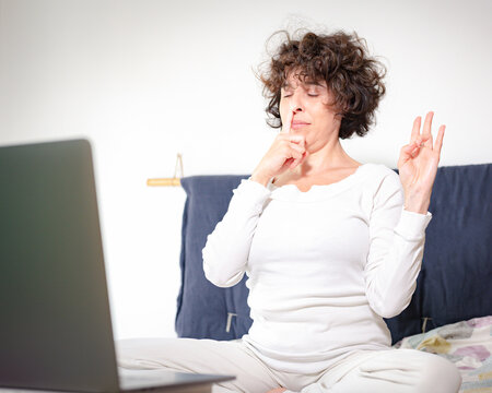 woman practicing yoga meditation and pranayama breathing, one finger blocks a nostril and the other hand is in surya mudra position, yoga online lessons in quarantine