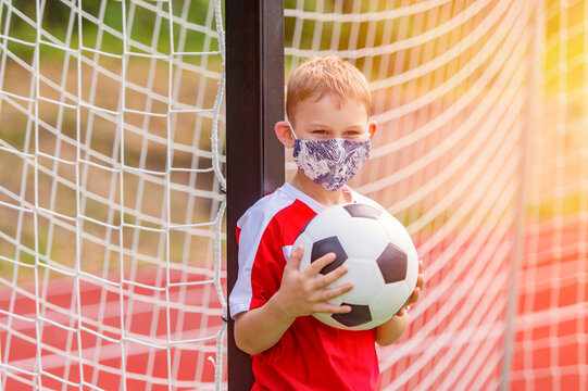 School kid with mask and soccer ball in a physical education lesson. Safe back to school during pandemic concept. Social distancing to fight COVID-19
