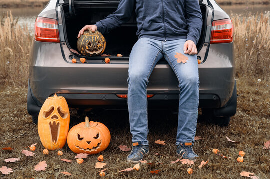 Crop view of adult man sitting in trunk of car with carved halloween pumpkins. Male legs in jeans near the car and a pumpkin jack-o-lantern, outdoors. Trick or trunk. Happy Halloween day.