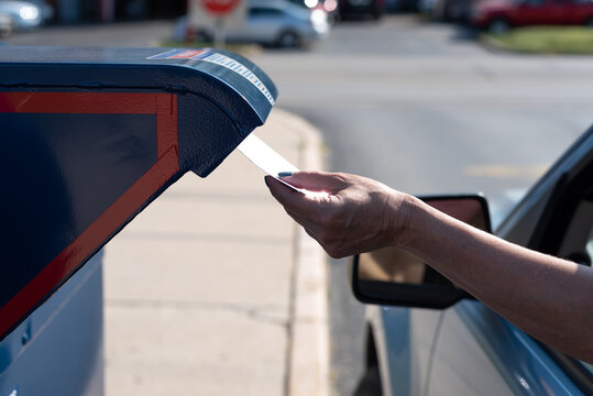 Palatine, IL/USA - 08-27-2020:  A woman is safely and contactlessly mailing in her application for ballot for 2020 election at the Post Office
