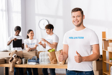 Selective focus of volunteer showing like gesture and looking at camera in charity center