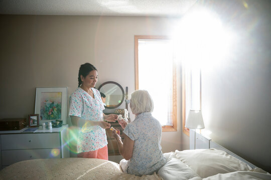 Home caregiver helping senior woman with medication in sunny bedroom
