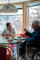 Home caregiver talking with senior man in wheelchair at table