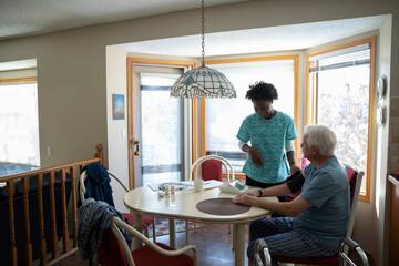Home caregiver checking blood pressure of senior man at kitchen table