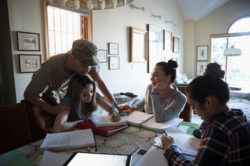 Soldier father and mother helping daughters with homework at dining ta