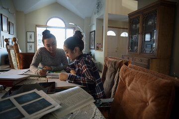 Mother helping daughter with homework at dining table