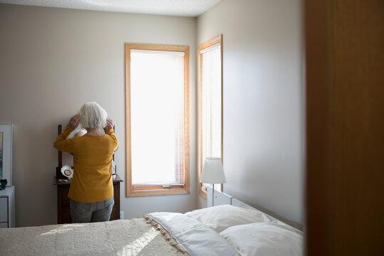 Senior woman fixing hair at mirror in bedroom