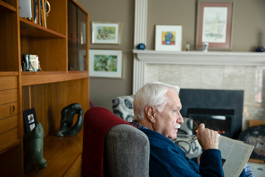 Thoughtful senior man reading magazine in living room