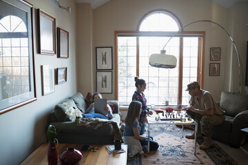 Soldier father playing chess with daughters in living room