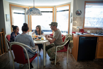Military family talking and eating breakfast at kitchen table