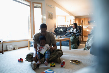 Soldier father and toddler son reading story in living room
