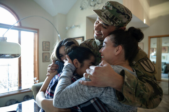 Affectionate military family hugging
