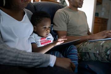Curious boy with digital tablet and military parents on sofa
