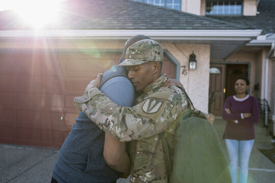 Mother watching son and father embracing each other and saying goodbye in driveway
