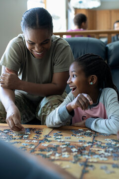 Laughing mother and daughter assembling jigsaw puzzle in living room