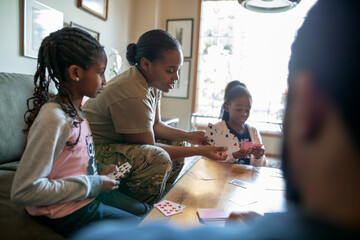 Army soldier mother playing cards with daughters in living room