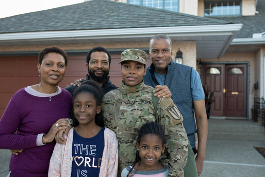 Portrait of smiling army soldier with her family in driveway