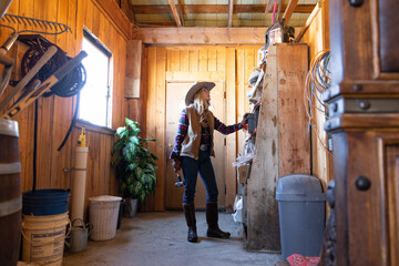Cowgirl looking at equipment on barn shelves