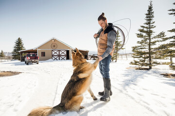 Male rancher shaking paw with dog on sunny snowy ranch