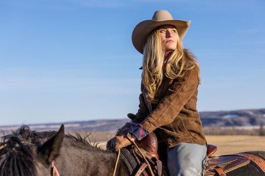 Thoughtful female rancher horseback riding on sunny ranch