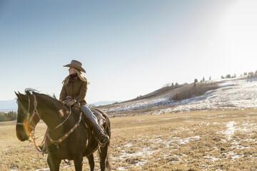 Female rancher horseback riding on sunny winter ranch