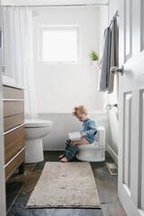 Boy sitting on training toilet reading book