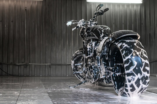 Wet and soapy black motorcycle at the car wash