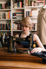 Young woman checking phone whilst sewing