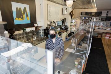 Portrait female barista in face mask working behind plexiglass in cafe