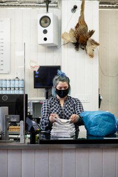 Female worker in face mask folding clean towels in market