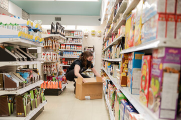 Female worker in face mask restocking food on shelves in market