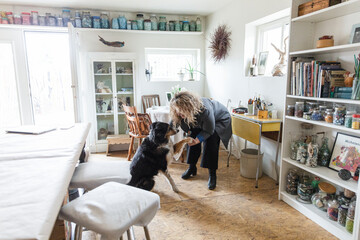 Female artist and dog shaking hands in home art studio
