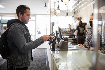 Male customer paying with smart phone at cafe counter