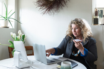 Woman talking on smart phone and working at laptop
