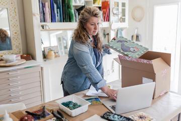 Female artist packaging mosaic art for e-commerce in home art studio