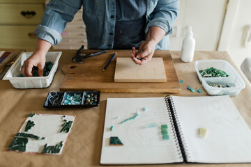 Female artist assembling mosaic project in art studio