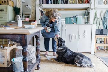 Female artist petting dog in home art studio