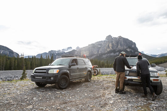 Brothers with map planning at overland SUV below sunny mountains